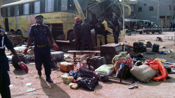 Security officers stand near abandoned items at the scene of a blast in the northern Nigerian city of Kano, on July 24, 2014. At least one person was killed and eight other people injured when a blast ripped through a crowded bus station in Kano, northern Nigeria, police and witnesses said today. The explosion happened at about 3:00pm (1400 GMT) at the New Motor Park in the predominantly Christian Sabon Gari neighbourhood, which has previously been targeted by Boko Haram militants. AFP PHOTO / Aminu ABUBAKAR